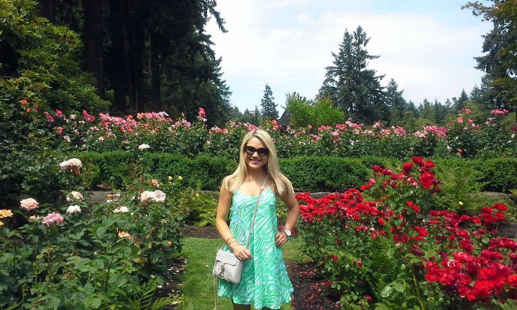 girl standing in a row of roses
