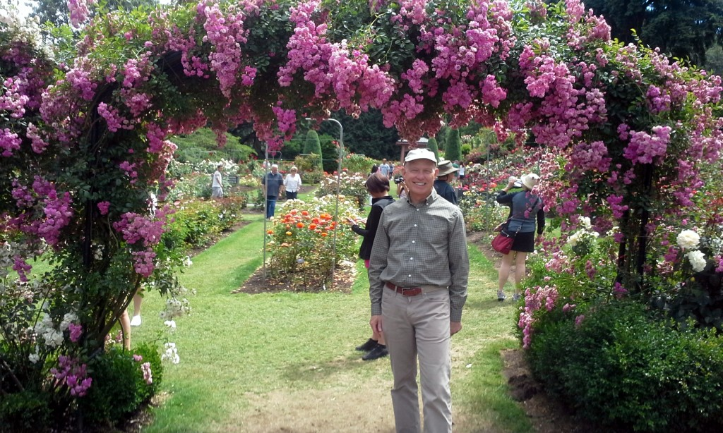 older man under rose garden arch