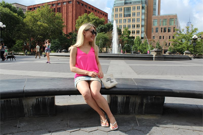 girl on a NY bench in a hot pink top and jean skirt Caitlin Hartley of Styled American http://styledamerican.com/first-week-in-new-york/