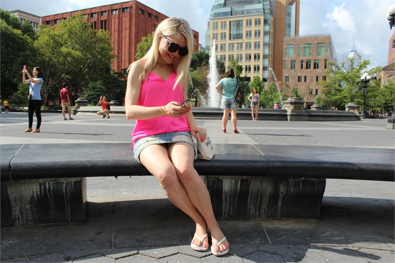girl looking at her phone on a bench Caitlin Hartley of Styled American http://styledamerican.com/first-week-in-new-york/