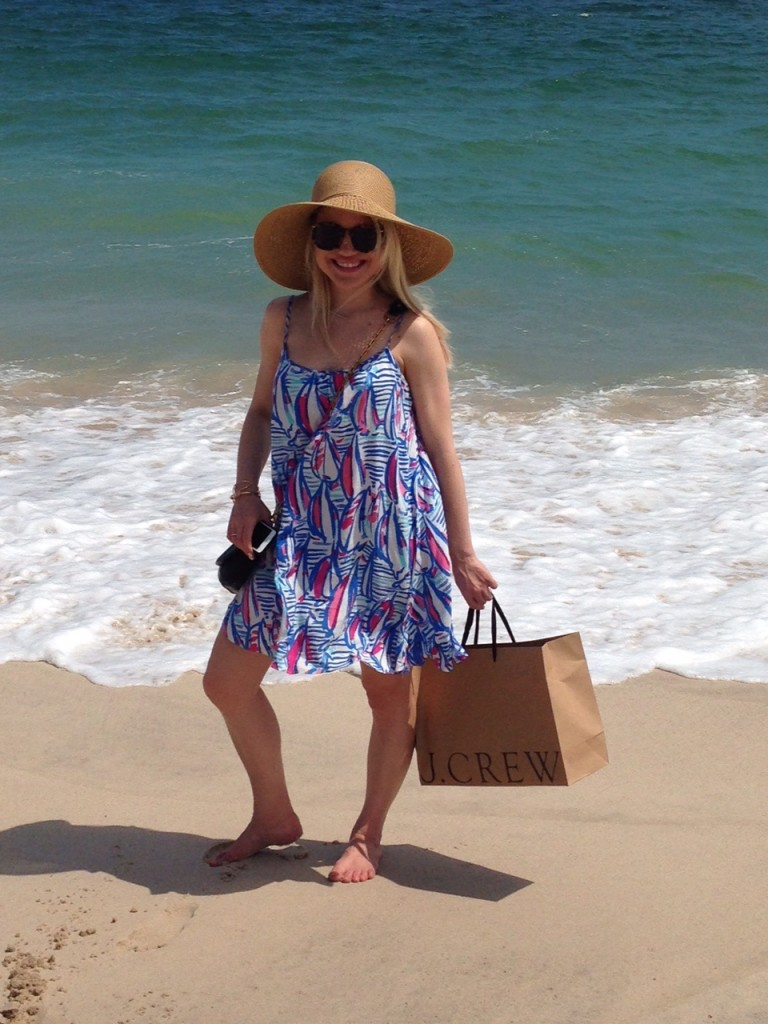 girl holding j.crew bag on the beach with sunhat and sundress Caitlin Hartley of Styled American