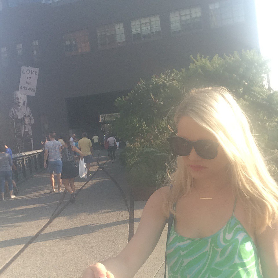 girl in front of love is the answer sign with Einstein on NYC's highline Caitlin Hartley of Styled American