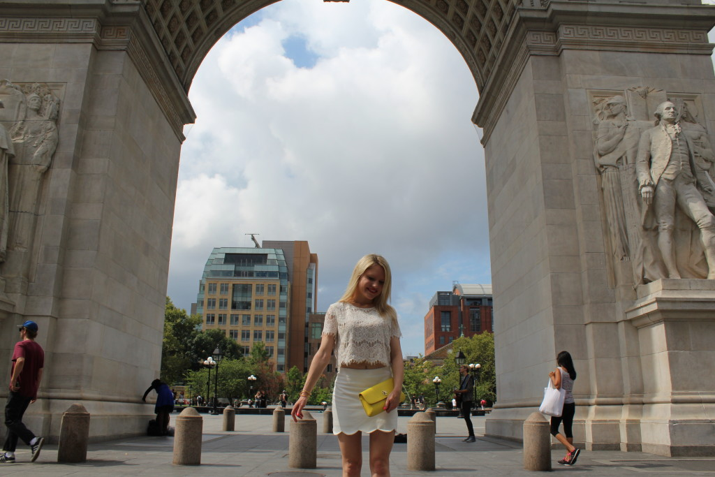 girl in lace crop top, scalloped skirt and clutch bag under Washington Square Park arches in NYC Caitlin Hartley of Styled American http://styledamerican.com/pop-of-yellow-2/