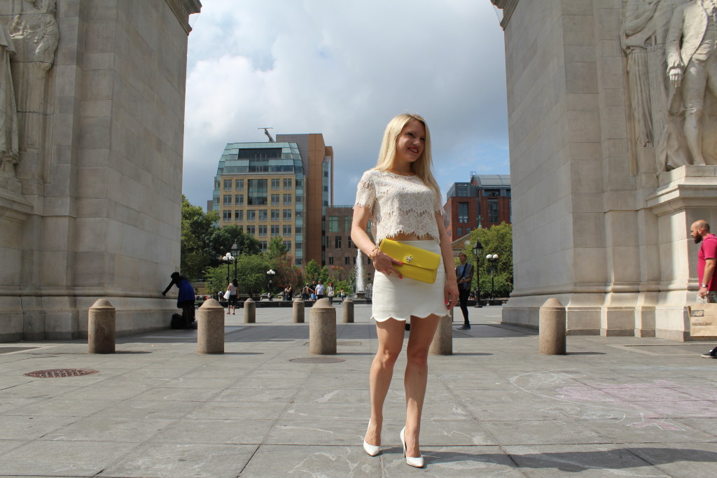 girl in white outfit standing under Washington Square Park arches Caitlin Hartley of Styled American http://styledamerican.com/pop-of-yellow-2/