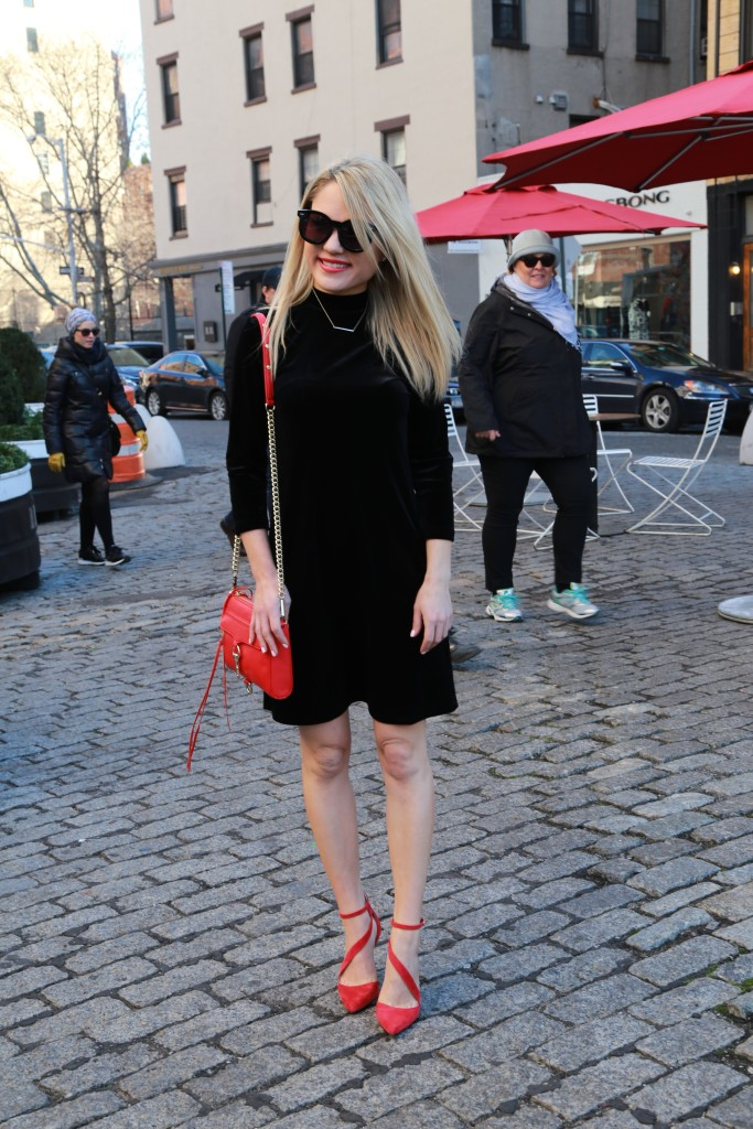 Caitlin Hartley of Styled American girl in black velvet dress, red bag and red pumps