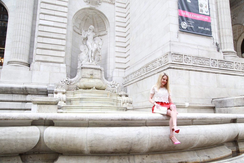 Caitlin Hartley of Styled American girl sitting on a fountain at nyc library