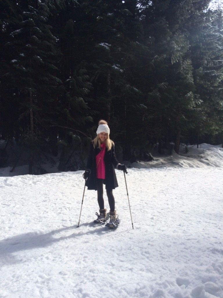 Caitlin Hartley of Styled American girl snow shoeing in black pants, pink sweater and pom pom hat
