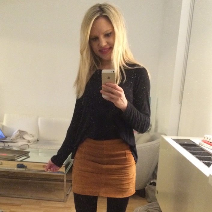 Caitlin Hartley of Styled American mirror pick in black long sleeve top and tan suede skirt