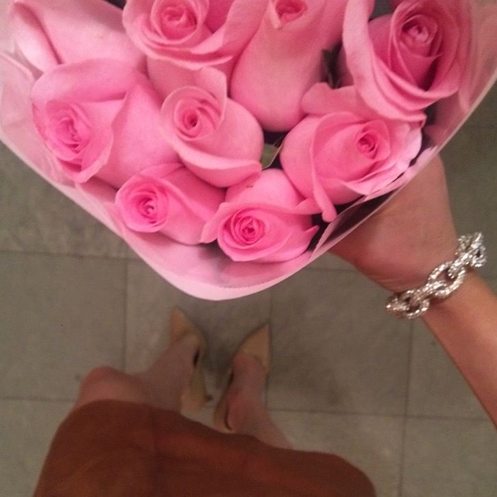 Caitlin Hartley of Styled American girl holding pink roses wearing bauble bracelet