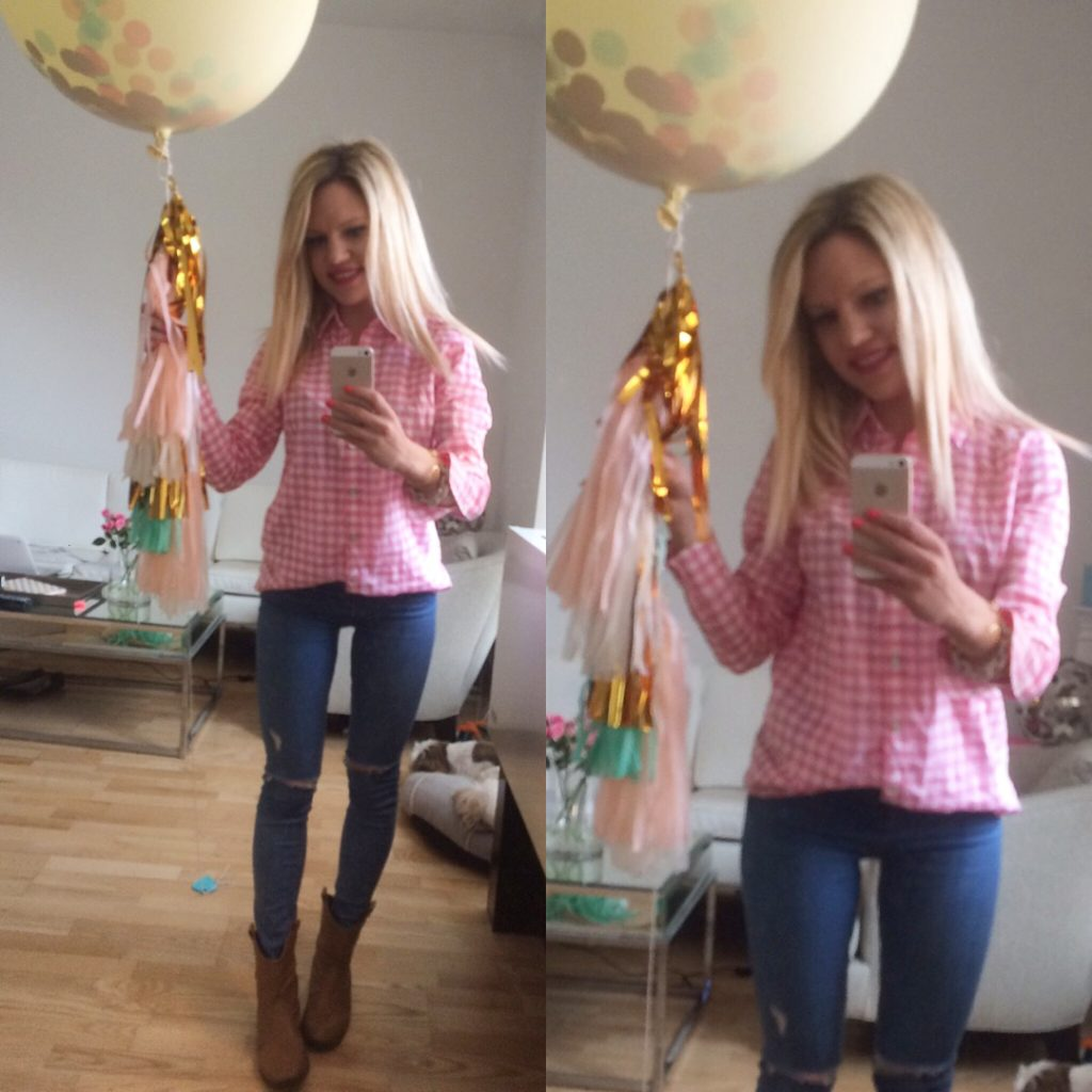 Caitlin Hartley of Styled American in a pink gingham top, skinny jeans, and holding a huge balloon with tassels