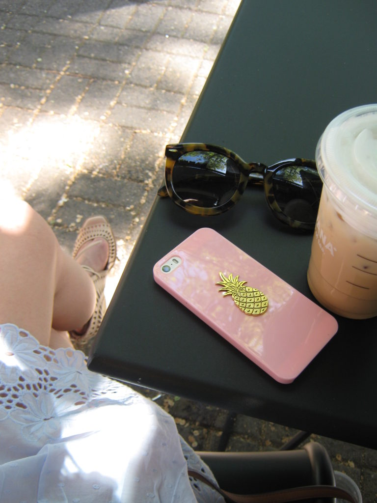 Caitlin-Hartley-of-Styled-American-at-acoffee-shop-pineapple-iphone-case-iced-starbucks-sunglasses