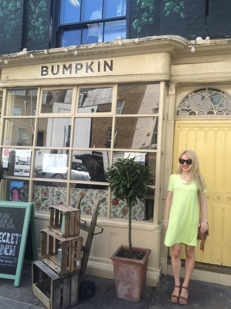 Caitlin-of-Styled-American-in-front-of-bumpkin-chelsea-in-yellow-dress-and-wedges