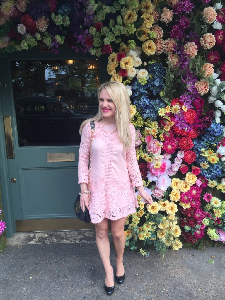 Caitlin-of-Styled-American-pink-lace-dress-black-bag-black-pumps-in-front-of-ivy-flower-wall