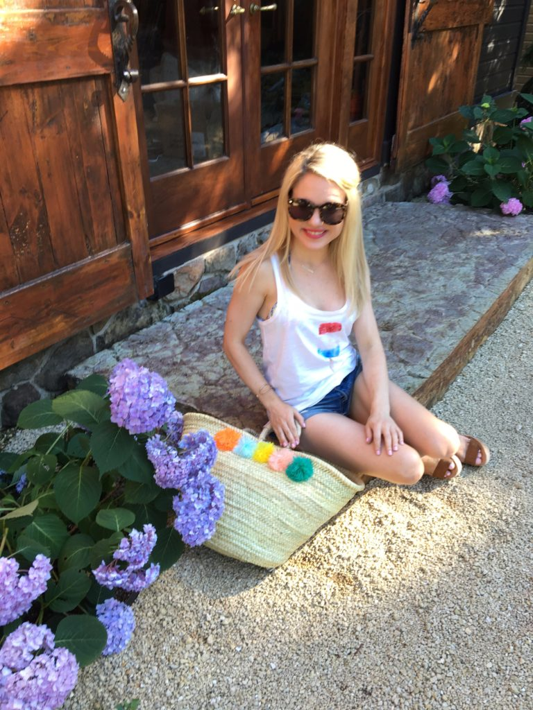 Caitlin-Hartley-of-Styled-American-in-popsicle-tank-top-distressed-jean-shorts-and-pop-pom beach-bag