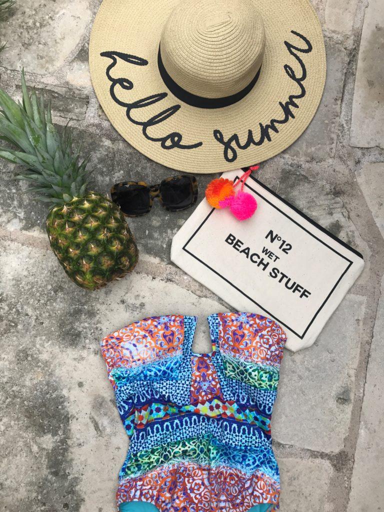 summer essentials, floppy hat, one piece suit, beach clutch
